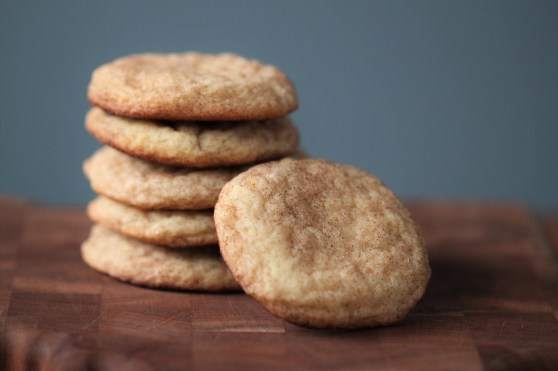 A stack of maple snickerdoodles sit in a pile, with one cookie leaned up against them in the foreground. They sit on a wooden surface against a blue background.