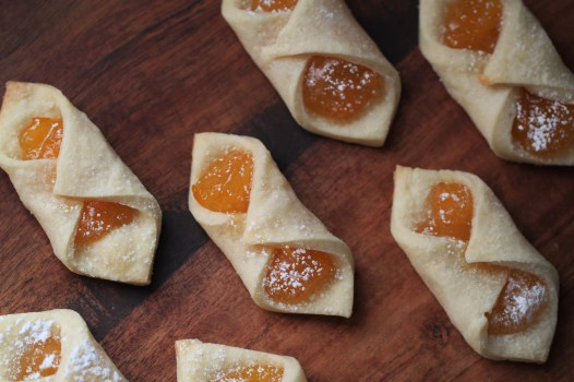Polish envelope cookies (Kolaczki) are filled with orange apricot jelly and are dusted with powdered sugar. They sit on a wooden surface.