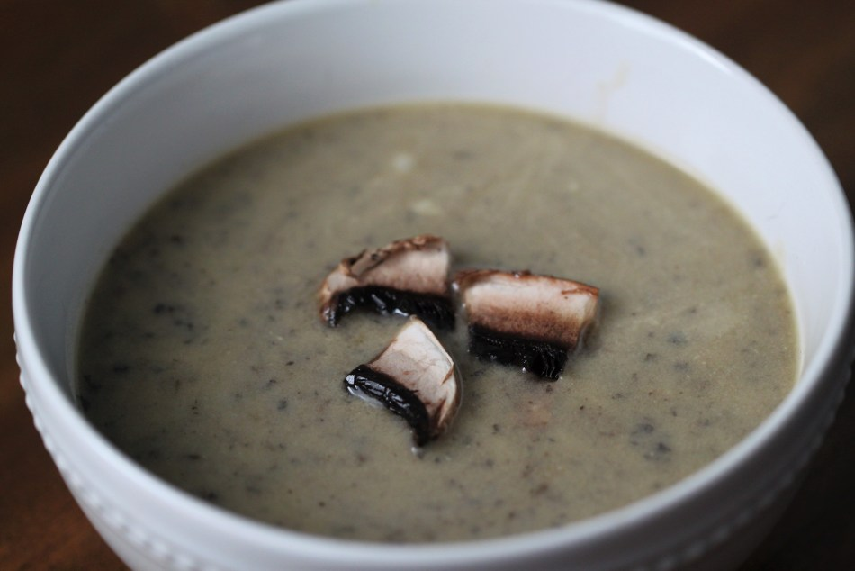 Creamy mushroom soup, garnished with three brown mushroom pieces, served in a white bowl against a wooden table background.