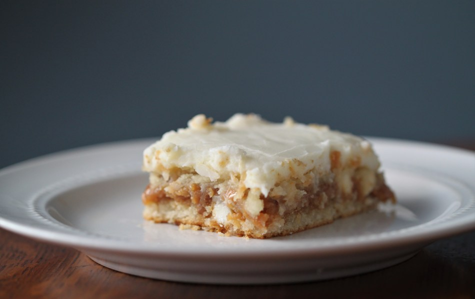 A slice of white chocolate turtle cake, with white chocolate icing and caramel center visible. It is sitting on a white plate with a blue background.