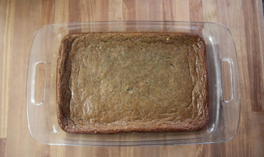 Baked persimmon pudding cake sits in a clear dish on a wooden surface. The edges are crinkly - evidence that the cake rose and subsequently fell with baking - but that is expected and normal with this recipe.