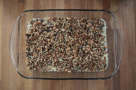Finely chopped pecans cover all of the previous ingredients. A bit of sweetened condensed milk is visible along the edges the 9 by 13 pan. The pan is transparent and sits on a wooden counter.