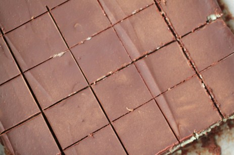 A top-down look at brownies that have been sliced. A cross-cut pattern is visible in the hard chocolate layer; you can barely see mint frosting and the brownie layer peeking through in the lower right portion of the image.