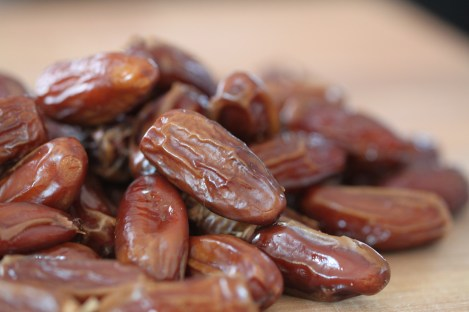 A pile of dates sits on a wooden surface.