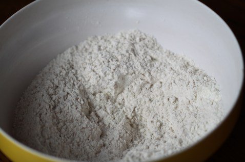 Flour (mixed with baking powder and spices) sits in a yellow bowl with a white interior.