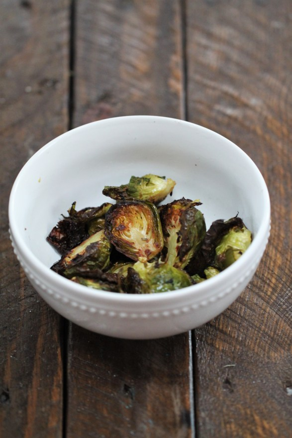 Brussels sprouts with crispy edges sit in a pile inside a white bowl, which sits on a wooden surface.