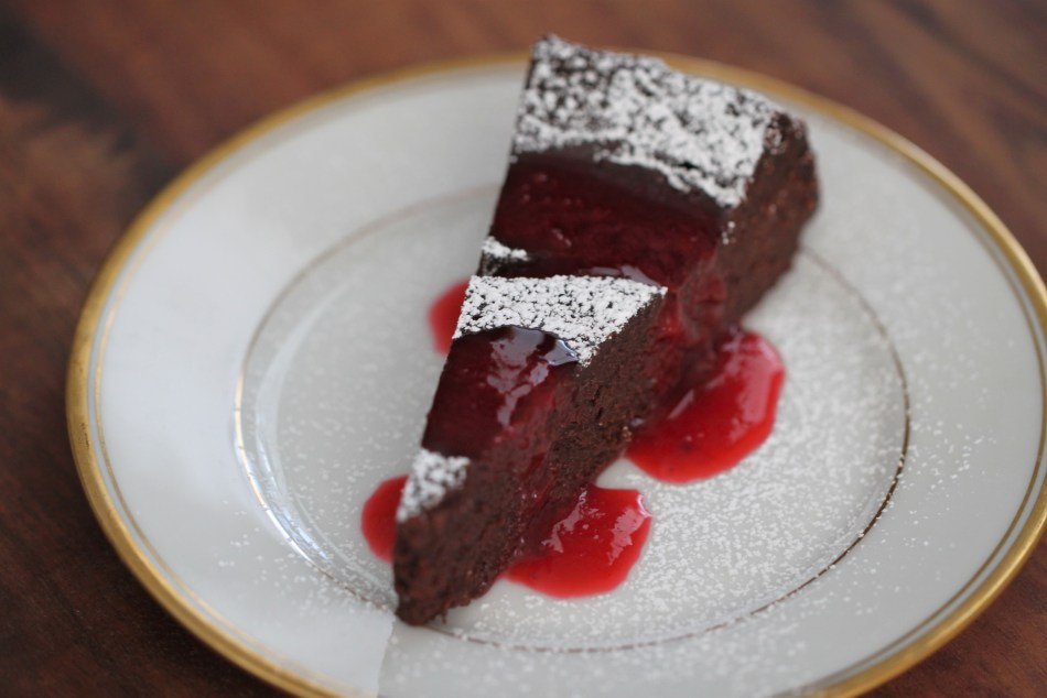 One slice of chocolate torte sits on a gold-rimmed china plate. The slice is dusted with powdered sugar and drizzled with bright red raspberry sauce.