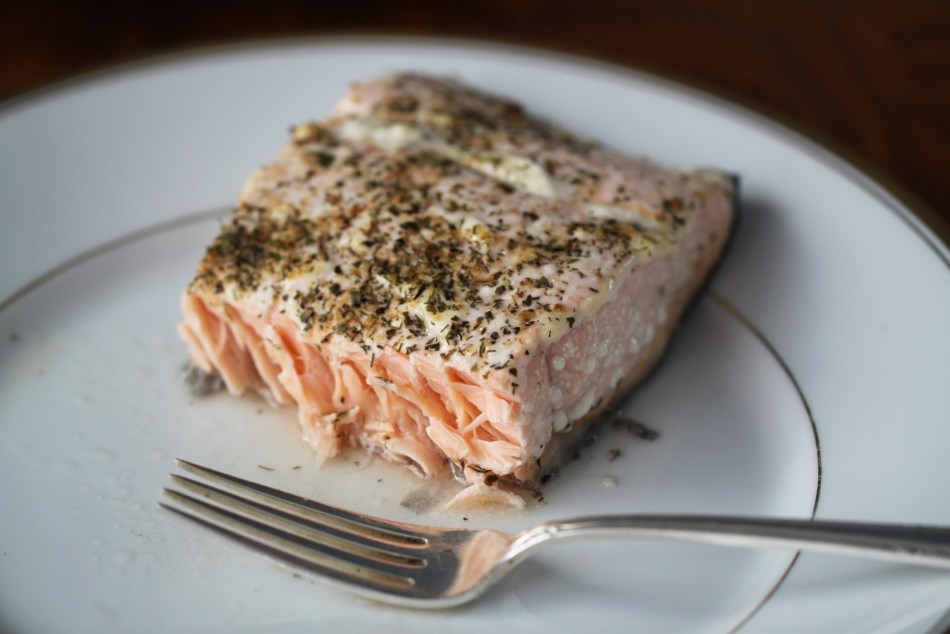 A baked, spiced salmon filet has been cut in half; the lightly pink flaky meat is visible. A fork rests in front of the filet; both the filet and the fork sit on a gold-rimmed white China plate.