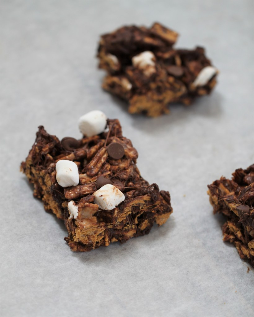 Three no-bake s'more bars sit on a white surface.