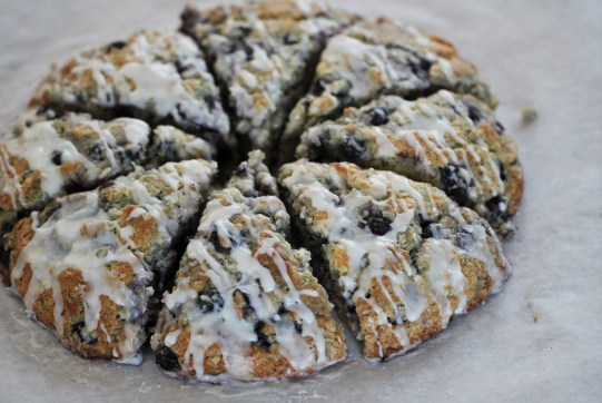 American-style blueberry scones are cut into wedges and sit in a circle atop a white surface. They are covered with a white, lemon glaze.