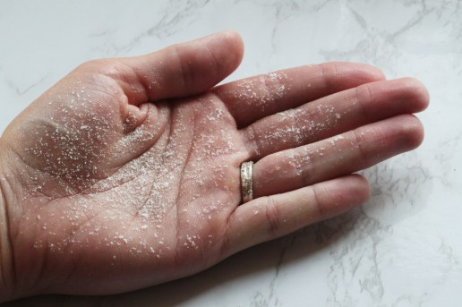 A Caucasian hand on a white background, slightly damp and covered in salt, ready to shape some onigiri.