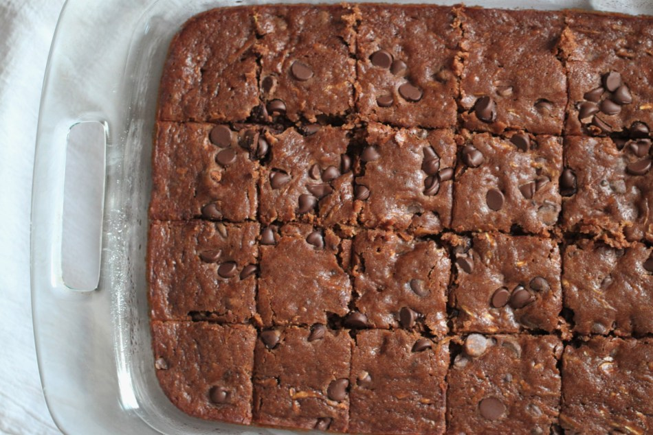 Baked, cooled, and sliced zucchini brownies, cut into squares while sitting in their pan