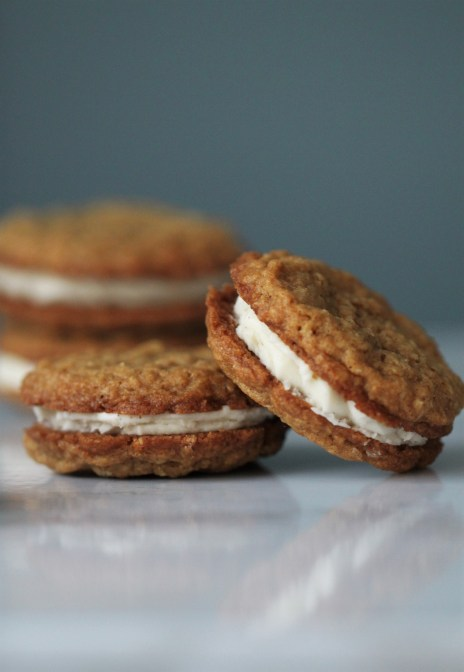 Freshly assembled oatmeal cream pie cookies lean against one another, sitting on a white surface against a blue backdrop.