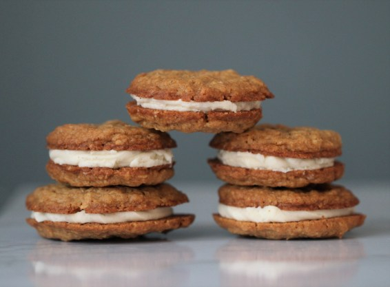 Two piles of two oatmeal cream pie cookies sit next to one another on a white surface, with a single oatmeal cream pie cookie balanced between them.