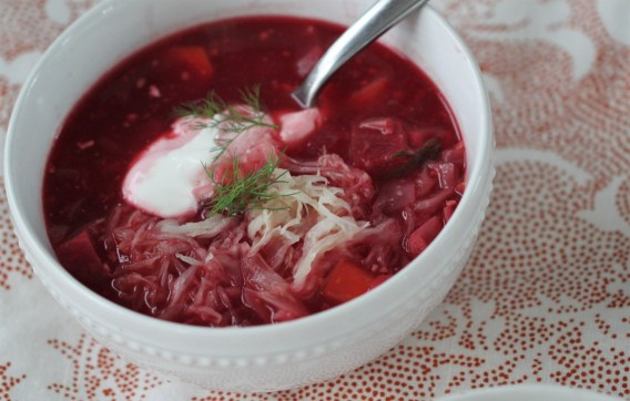A bowl of borscht, garnished with sauerkraut, dill, and sour cream, sitting in a white bowl on a red and white tablecloth.