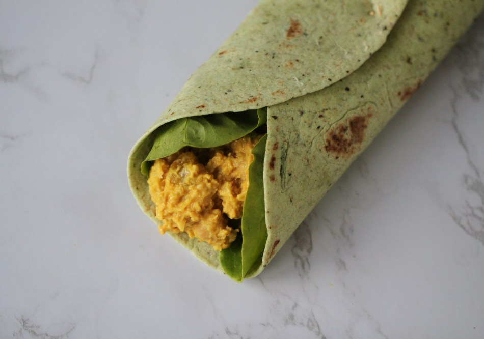 Vegan coronation chicken is a yellow salad made from mashed chickpeas . It rests inside a set of spinach leaves, folded within a green tortilla, which sits on a white marble surface.