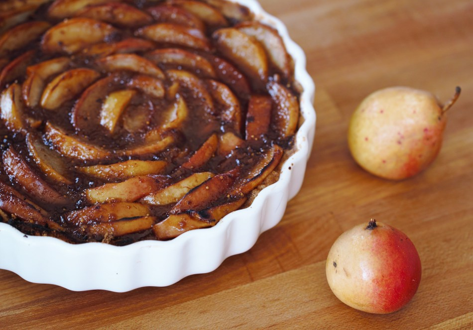 A pear fig tart, with the pears arranged in concentric circles, sits in a white tart pan on a wooden surface. Two yellowish red pears sit next to the pear tart.