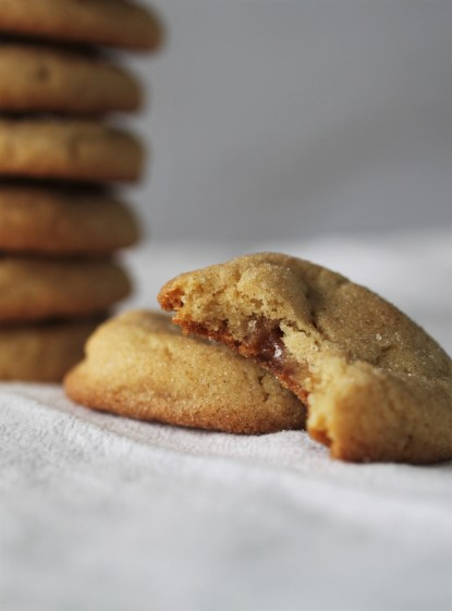 A caramel-filled snickerdoodle with a bite taken out of it (showing the caramel inside) leans on an intact cookie. A pile of caramel filled snickerdoodles rests in the background.