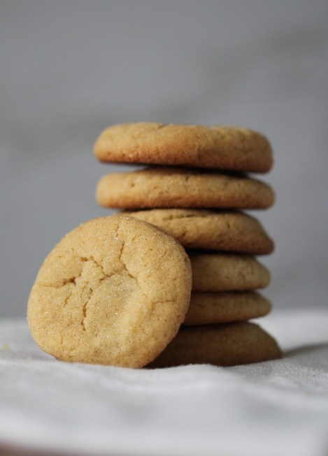 A stack of 6 caramel filled snickerdoodles sits on top of a white surface. One cookie rests against the stack, facing the viewer.