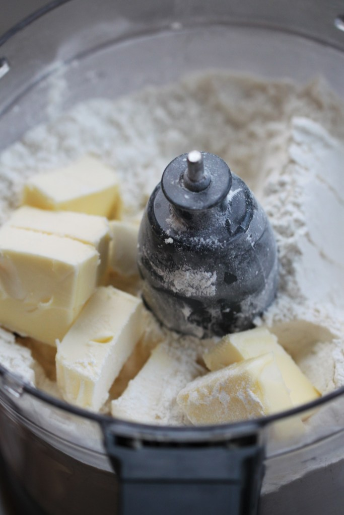 The first ingredients for sweet shortcrust pie dough - flour, powdered sugar, and cubes of cold butter - sit in the bowl of a food processor.