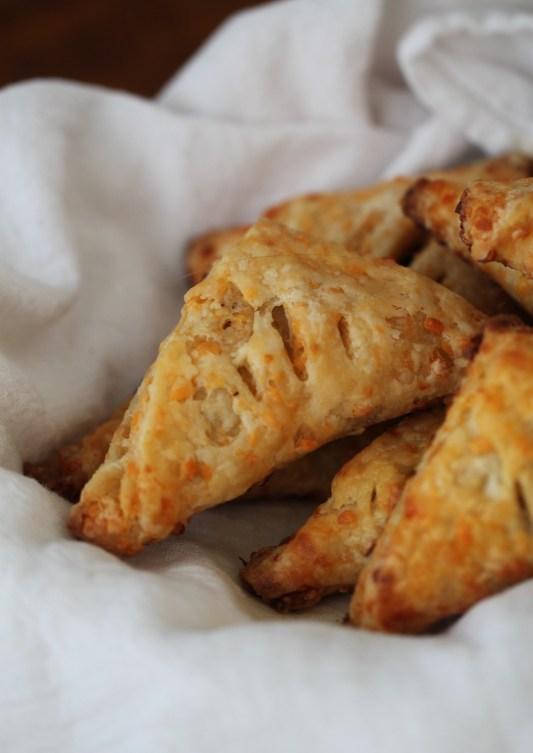 Several triangular mushroom turnovers sit piled in a bowl lined with white cloth.