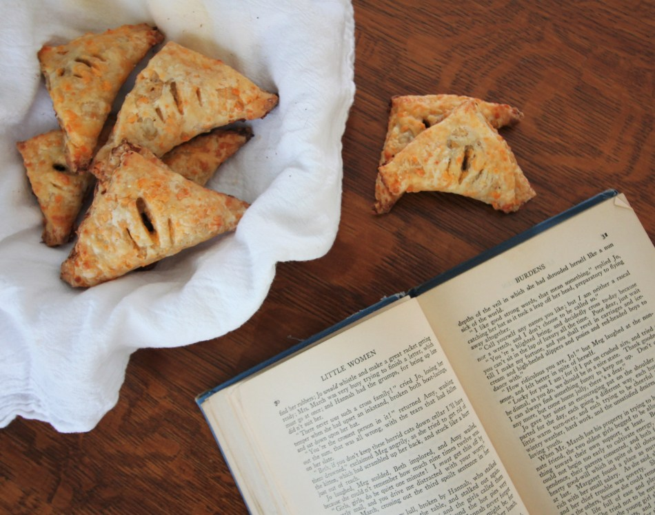 """Several savory turnovers - golden triangular pockets, with obvious cheese in the dough - sit in a white bowl and on a wooden surface. An old copy of Little Women sits adjacent to the turnovers, open to the chapter """"Burdens""""."""