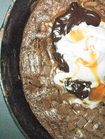Brownies baked in a skillet with ice cream, fudge, caramel and whipped cream on top