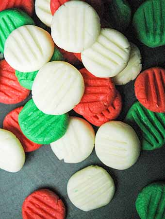 Red, white and green holiday cream cheese dinner mints scattered on a black background.