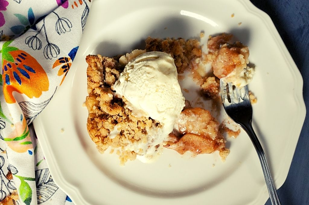 Close up view of apple pie slice with vanilla ice cream on top. Placed on top of a white plate.