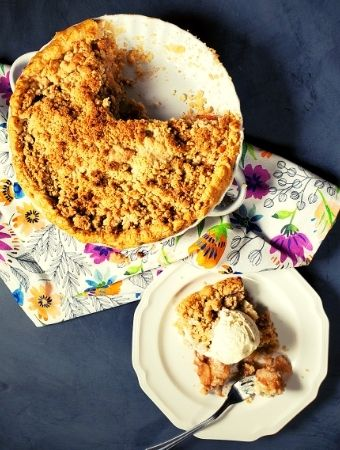Slice of apple pie on plate with ice cream on top pictured next to a apple pie with crumble topping with slices missing.
