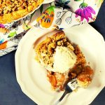 Slice of apple pie on plate with ice cream on top pictured next to the apple pie.