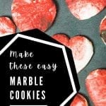 red and white marbled cut out heart cookies on black background