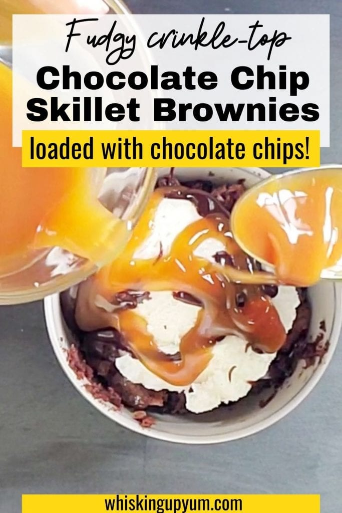 Text says fudgy crinkle-top chocolate chip skillet brownies with loads of chocolate chips!. Image shows a spoon scooping caramel sauce onto brownies with ice cream on top that is sitting in a white bowl that is on top of a charcoal background. Brownies in a skillet with a spoon sitting to the left of the bowl of brownies.