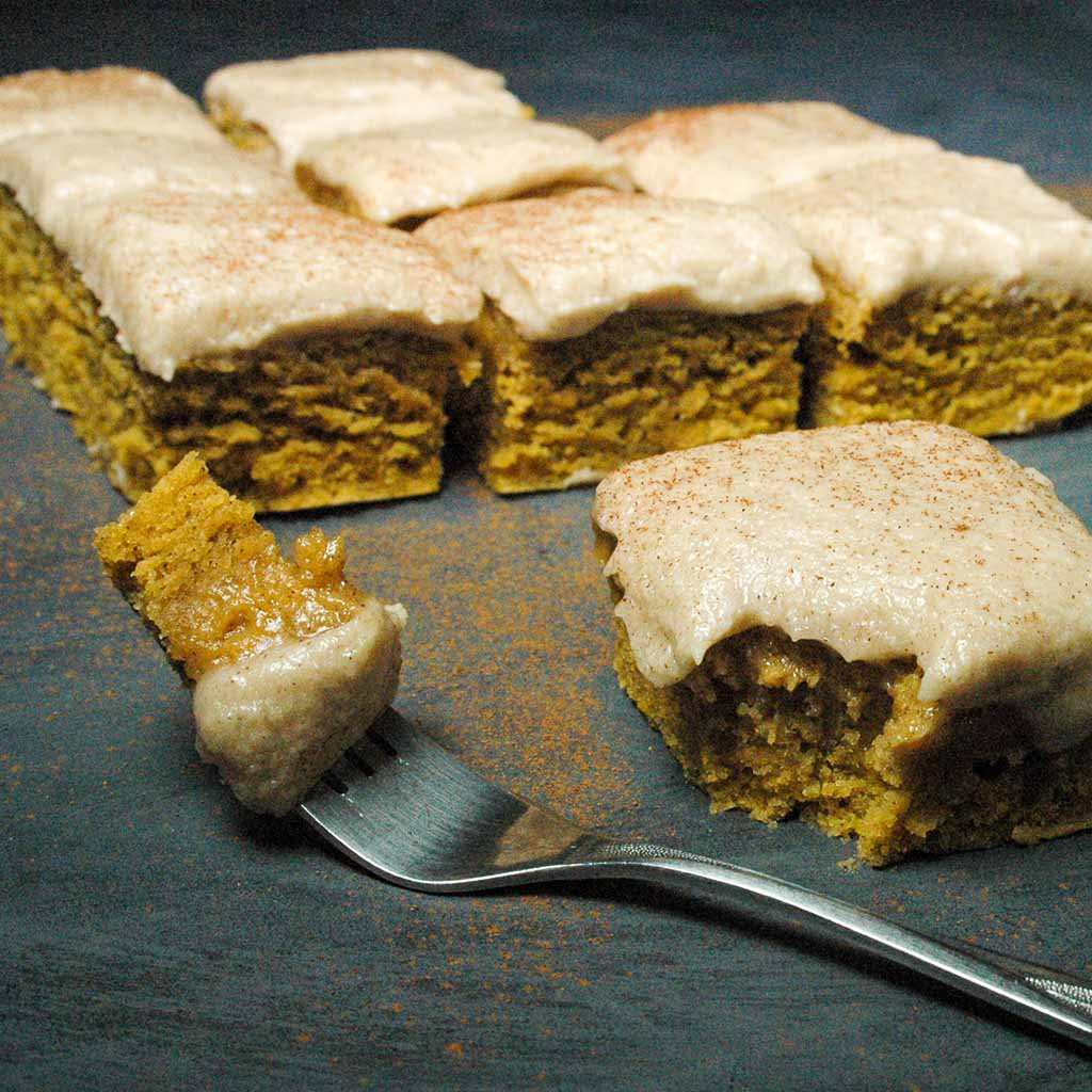 Pumpkin pie bars with brown sugar frosting in background with a bite sized piece on fork.