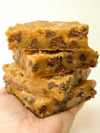 Hand holding stack of four Salted Caramel Chocolate Chip Cookie Bars