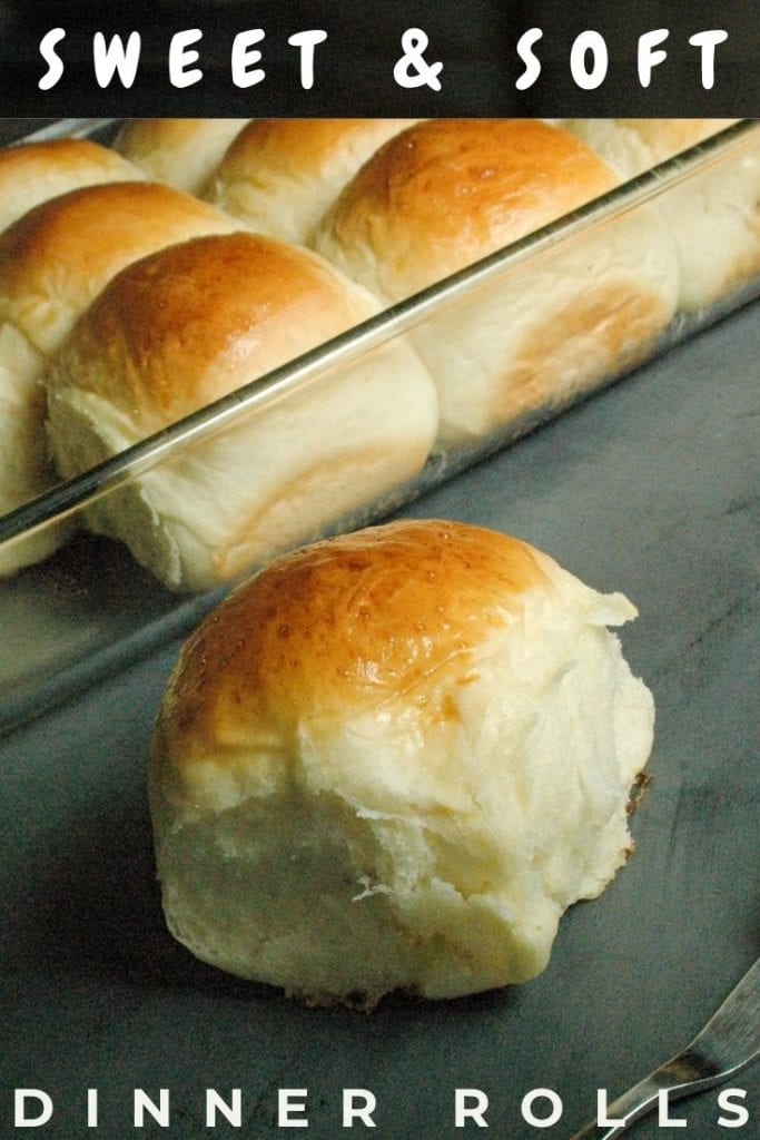 One sweet homemade dinner roll placed in front of a 9x13 glass pan filled with rolls.