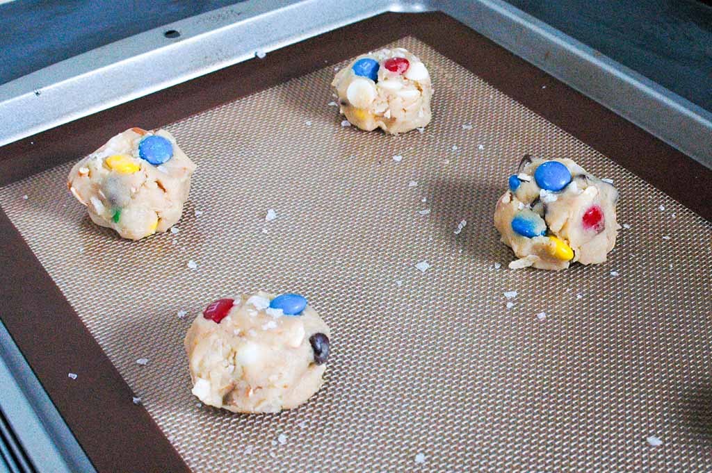 Dough balls ready to go in the oven. Thick trash cookies, also known as kitchen sink cookies, loaded with potato chips, pretzels, m&ms, chocolate chips, peanut butter cups and sprinkles.