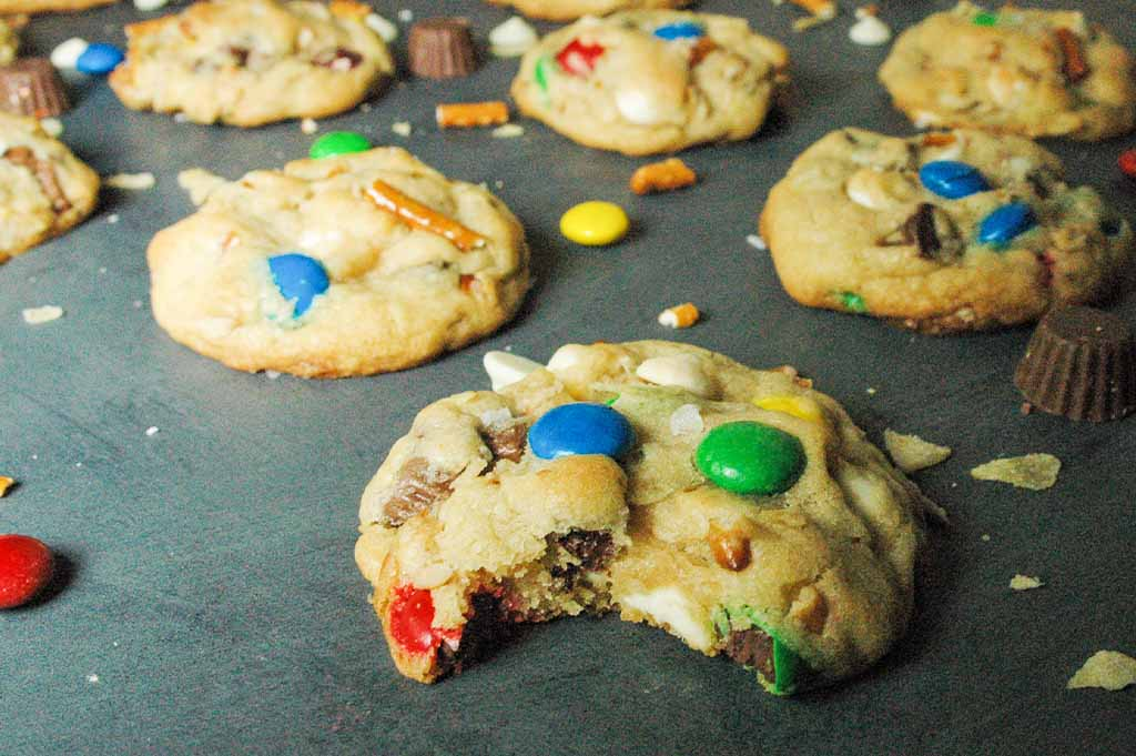 Thick trash cookies, also known as kitchen sink cookies, loaded with potato chips, pretzels, m&ms, chocolate chips, peanut butter cups and sprinkles. One cookie has a bite out of it.