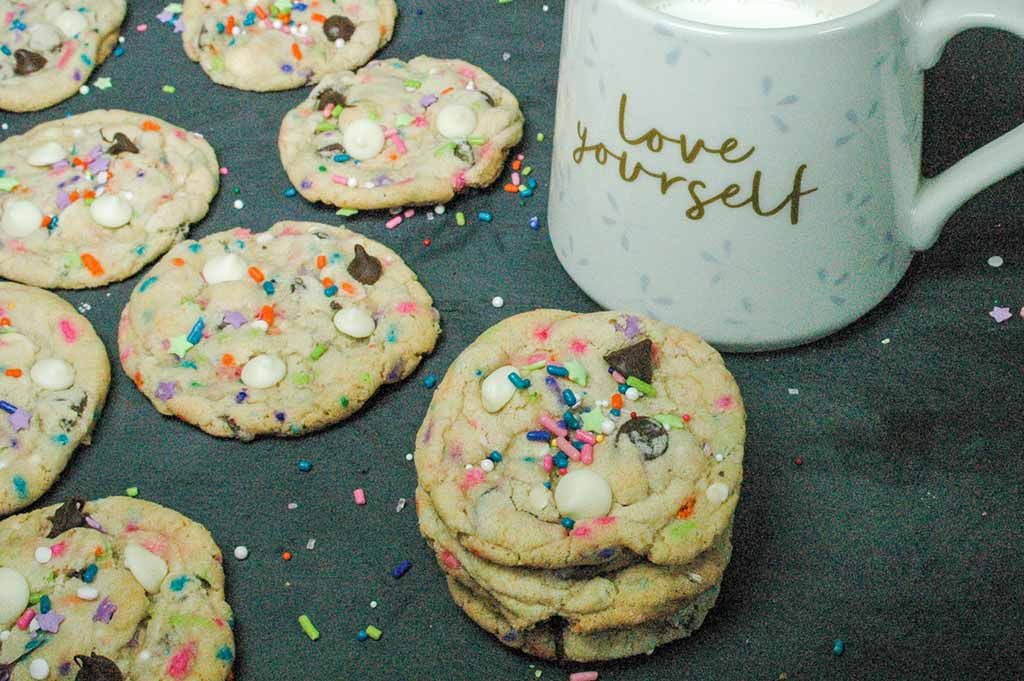 Birthday cake cookies loaded with sprinkles and chocolate chips scattered on a black background and milk in a coffee cup.