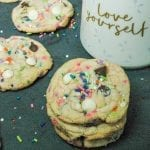 Birthday cake cookies loaded with sprinkles and chocolate chips stacked on top of each otheron a black background and milk in a coffee cup.