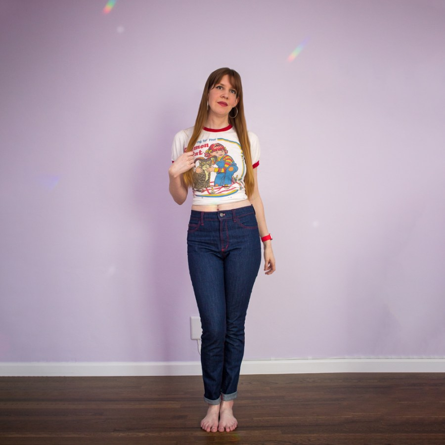 girl in handmade denim jeans with red topstitching standing against a lilac wall