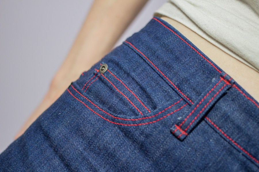closeup detail shot of handmade jeans with red topstitching front pocket