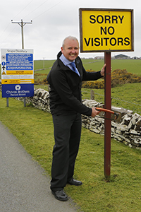 "Scapa Distillery Manager Brian Macaulay removes the ""No Visitors"" sign at the distillery entrance following the opening of Scapa's new visitor center. Photo courtesy Chivas Brothers."