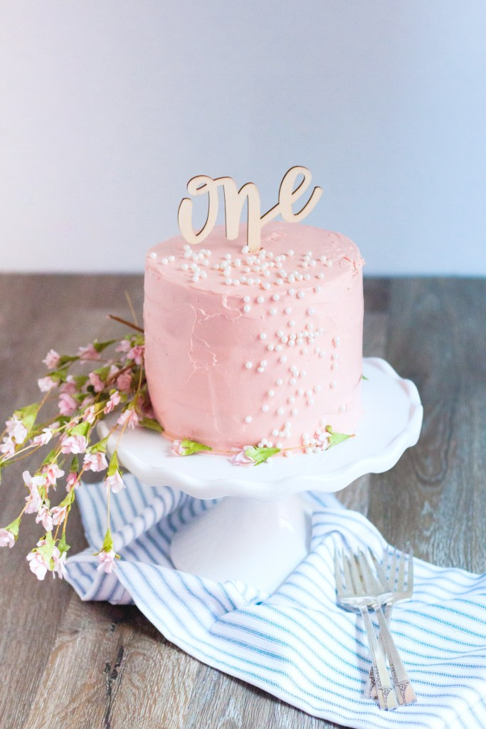 Baby's First Organic Birthday Cake on a stand with small pink flowers and blue striped kitchen cloth.