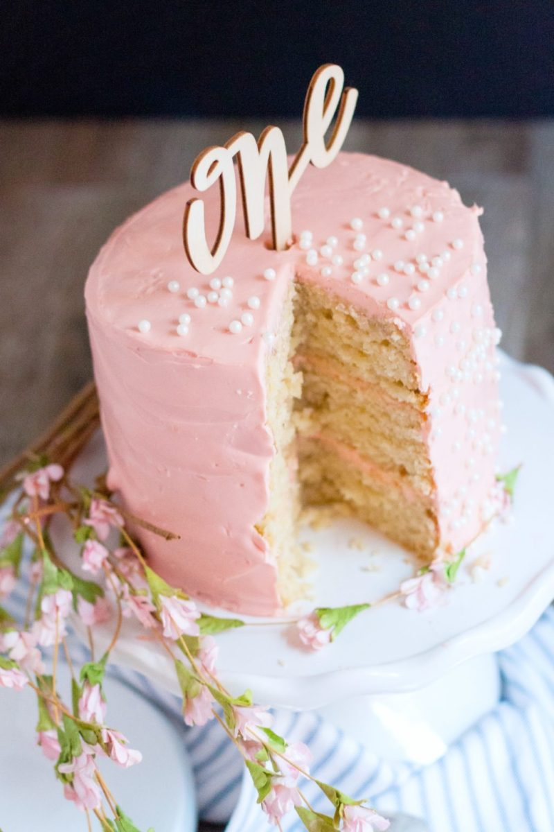 """The """"one"""" cake topper is added and the cake is topped with edible pearls, sliced and ready to serve."""