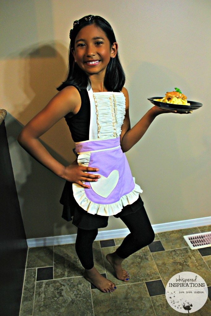 A little girl holds her plate and shows off her apron.