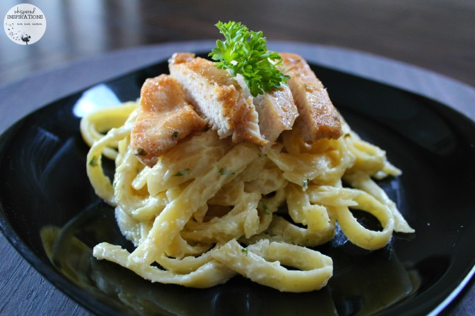 Delicious pan-friend chicken tops fettucine alfredo pasta.