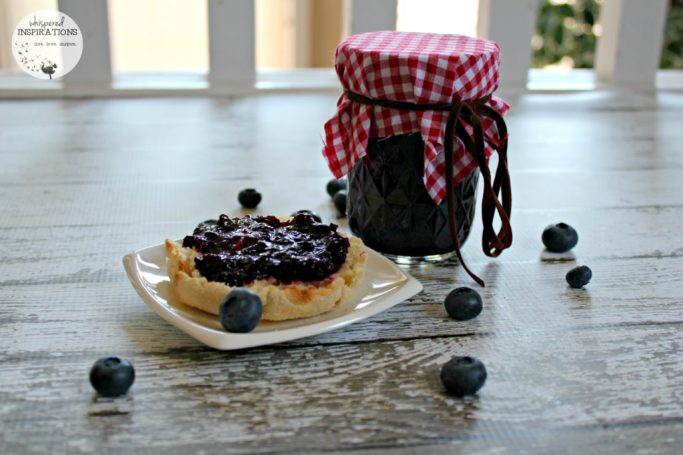 Organic blueberry jam recipe is spread on an English muffin.