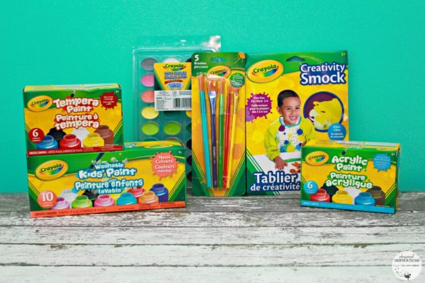 Crayola paint brushes, paint and paint smock are displayed against a teal background.