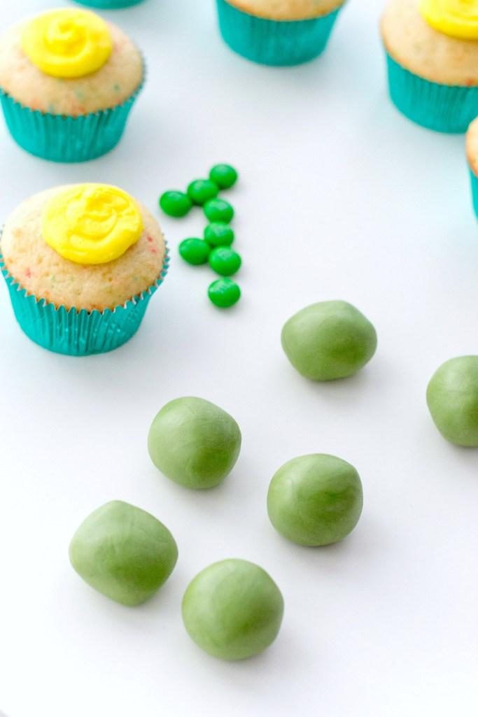 Green fondant rolled into balls alongside iced funfetti cupcakes.
